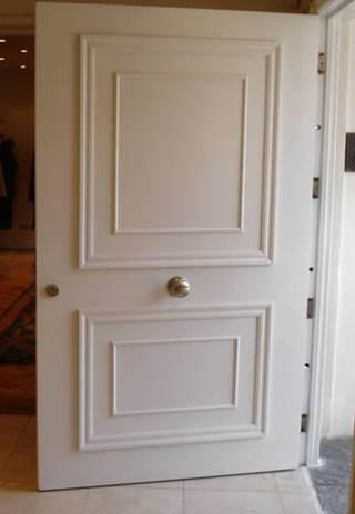 Puerta de seguridad para departamentos con moldura blanca